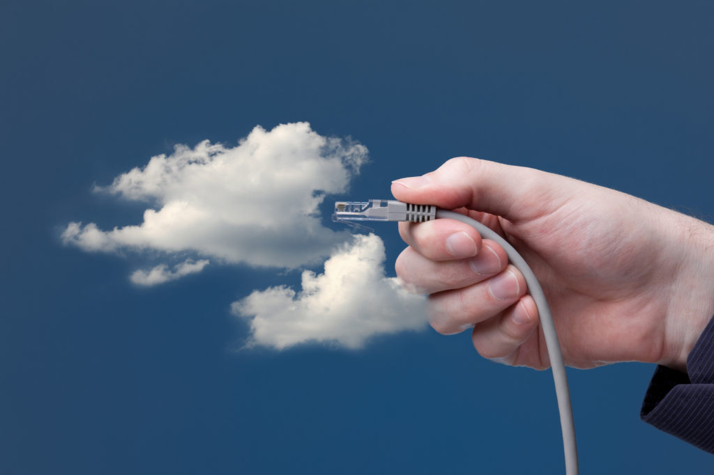 Cloud computing concept. Hand with ethernet cable connecting into cloud.